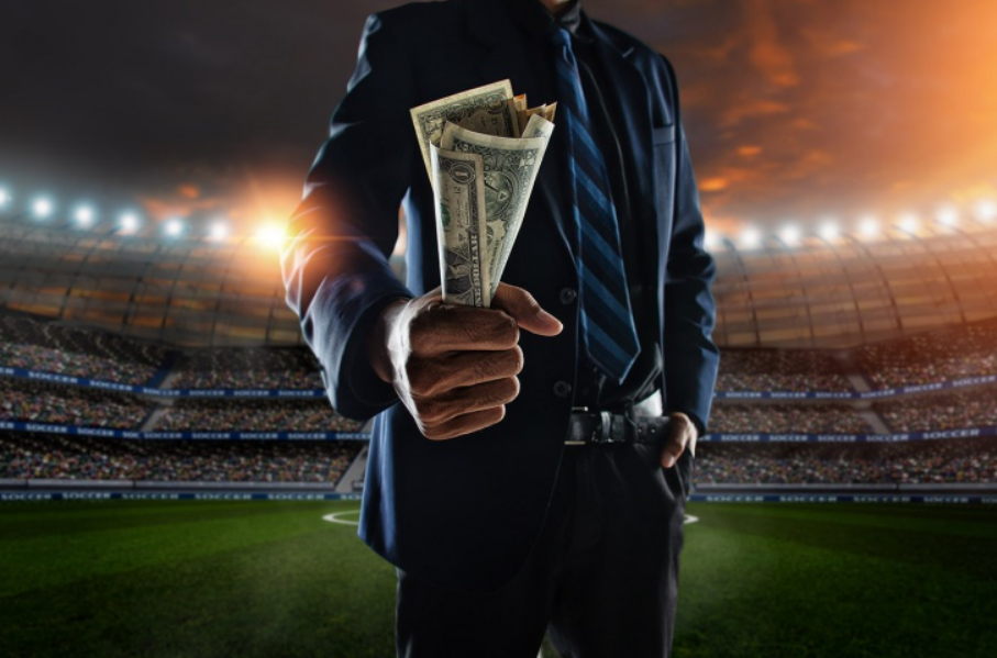 A man holding cash in his hand on the football field